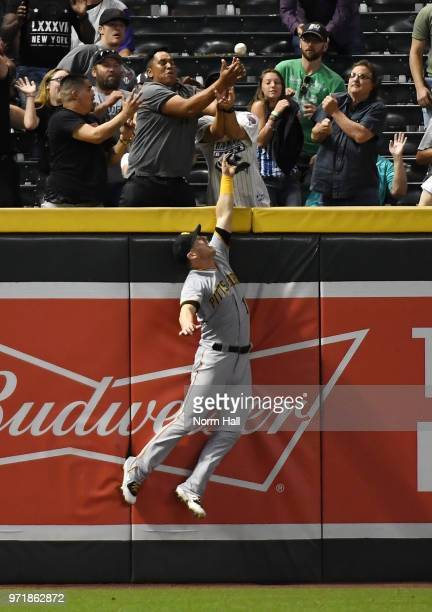 Corey Dickerson of the Pittsburgh Pirates crashes into the left field wall and cannot make a catch on a three run home run by Jake Lamb of the...