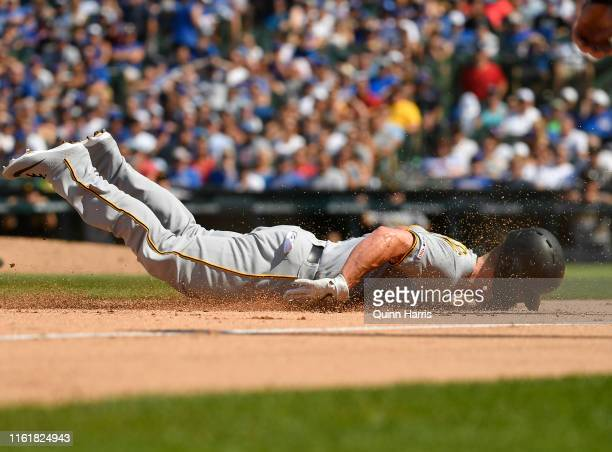 Corey Dickerson of the Pittsburgh Pirates hits his head sliding to third base in the seventh inning against the Chicago Cubs at Wrigley Field on July...