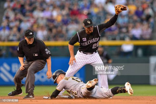Corey Dickerson of the Pittsburgh Pirates reaches second base after a single and a Colorado Rockies error ahead of a tag attempt by Nolan Arenado of...