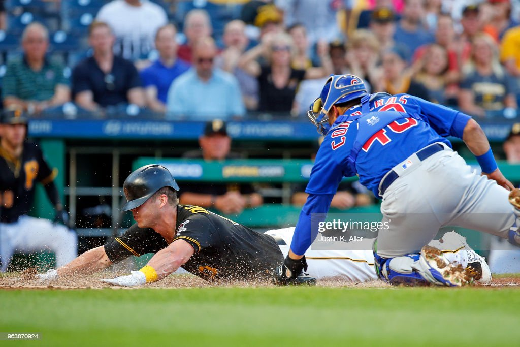 Corey Dickerson #12 of the Pittsburgh Pirates scores on a sacrifice fly in the second inning against Willson Contreras #40 of the Chicago Cubs at PNC Park on May 30, 2018 in Pittsburgh, Pennsylvania.