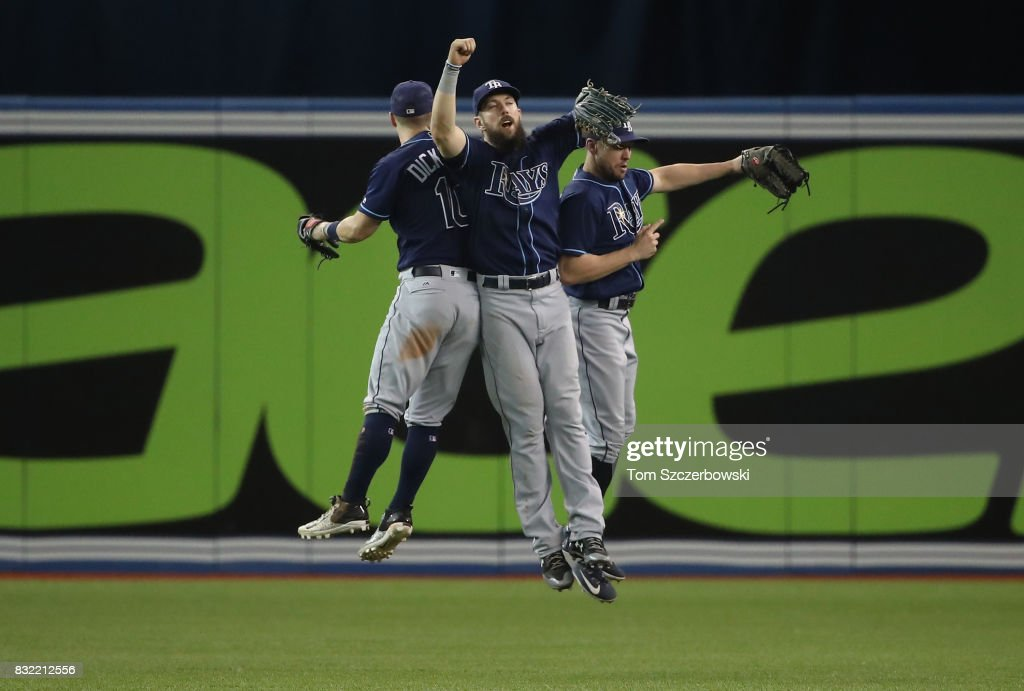 Corey Dickerson #10 of the Tampa Bay Rays celebrates a victory with Steven Souza Jr. #20 and Peter Bourjos #18 after MLB game action against the Toronto Blue Jays at Rogers Centre on August 15, 2017 in Toronto, Canada.