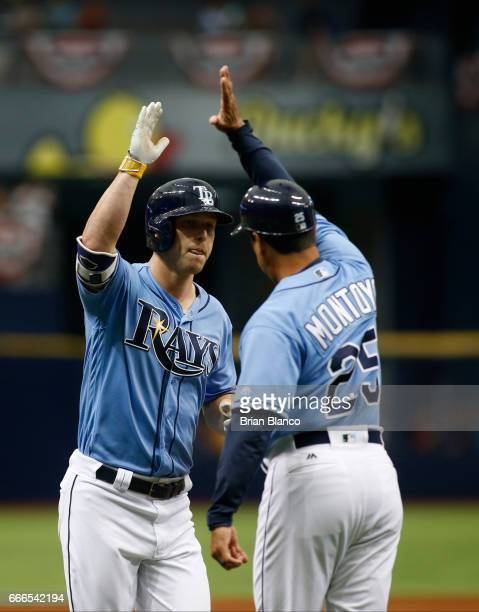 Corey Dickerson of the Tampa Bay Rays celebrates with third base coach Charlie Montoyo after hitting a home run in the third inning of a game on...