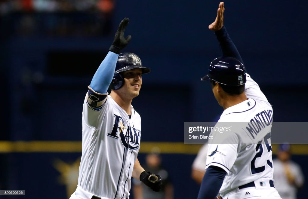 Corey Dickerson #10 of the Tampa Bay Rays celebrates with third base coach Charlie Montoyo #25 as he rounds third base after hitting a home run off of pitcher Yu Darvish of the Texas Rangers during the during the sixth inning of a game on July 21, 2017 at Tropicana Field in St. Petersburg, Florida.