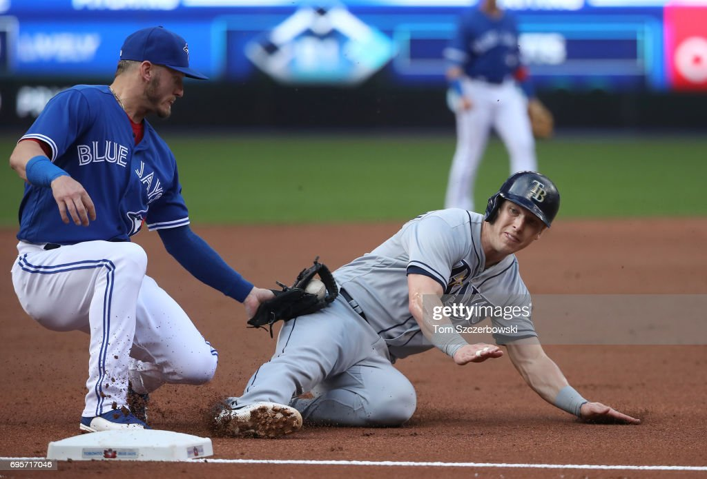 Corey Dickerson #10 of the Tampa Bay Rays is caught stealing third base in the first inning during MLB game action as Josh Donaldson #20 of the Toronto Blue Jays tags him out at Rogers Centre on June 13, 2017 in Toronto, Canada.