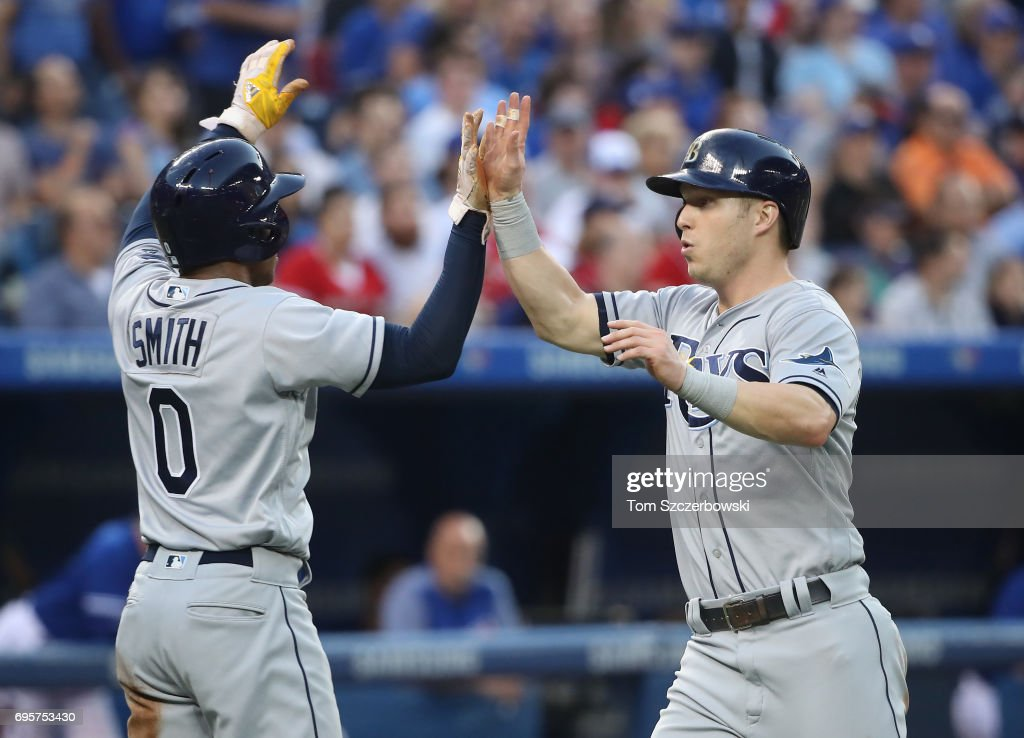 Corey Dickerson #10 of the Tampa Bay Rays is congratulated by Mallex Smith #0 after both runners scores on a two-run double by Evan Longoria #3 in the fourth inning during MLB game action against the Toronto Blue Jays at Rogers Centre on June 13, 2017 in Toronto, Canada.