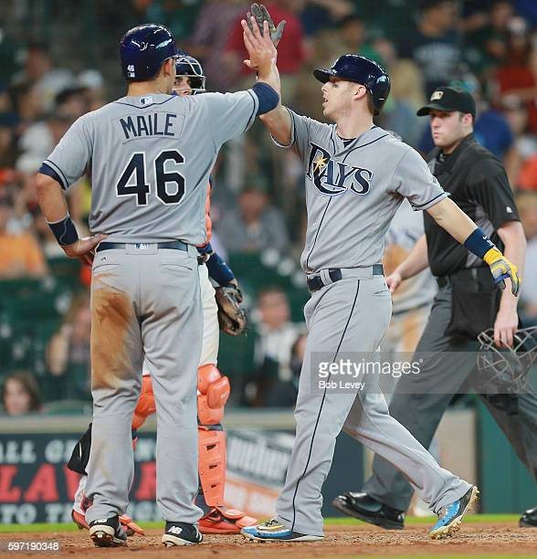 Corey Dickerson of the Tampa Bay Rays receives a high five from Luke Maile afer hitting a three run home run in the eighth inning against the Houston...