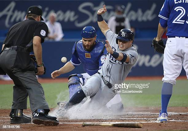 Corey Dickerson of the Tampa Bay Rays slides across home plate to score a run in the fourth inning during MLB game action as Russell Martin of the...