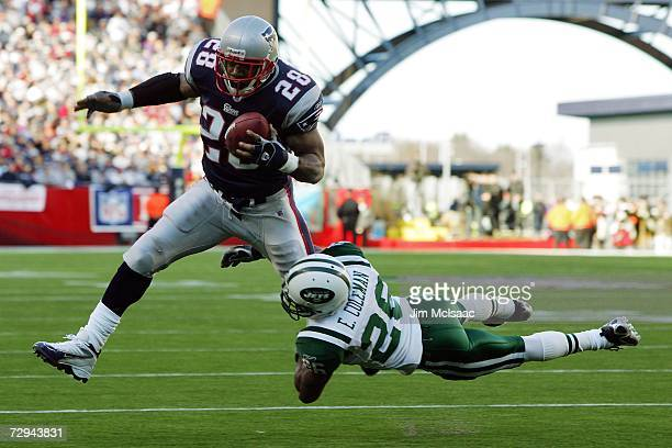 Corey Dillon of the New England Patriots runs with the ball as Erik Coleman of the New York Jets tries to tackle him during the AFC Wild Card Playoff...