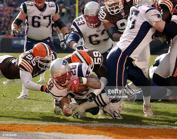 Corey Dillon of the New England Patriots scores a touchdown as Clevealnd Browns players Barry Gardner and Kevin Bently attempt the stop during the...