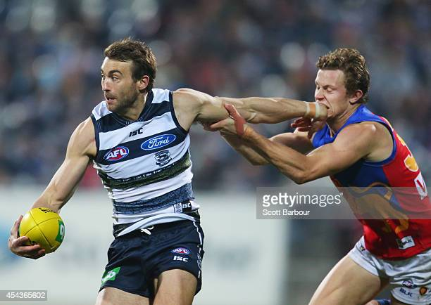 Corey Enright of the Cats is tackled during the round 23 AFL match between the Geelong Cats and the Brisbane Lions at Simonds Stadium on August 30,...