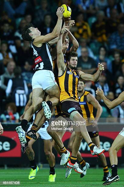 Corey Gault of the Magpies marks the ball over Ben Stratton of the Hawks during the NAB Challenge AFL match between Hawthorn Hawks and the...