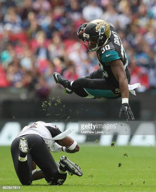 Corey Grant of the Jacksonville Jaguars is tackled Tony Jefferson of the Baltimore Ravens during the NFL International Series match between Baltimore...