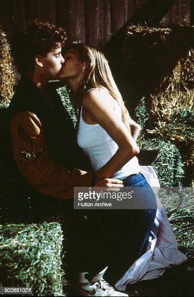 Corey Haim is kissed by Lala Sloatman in a scene from the Universal Studio movie 'Watchers' circa 1988