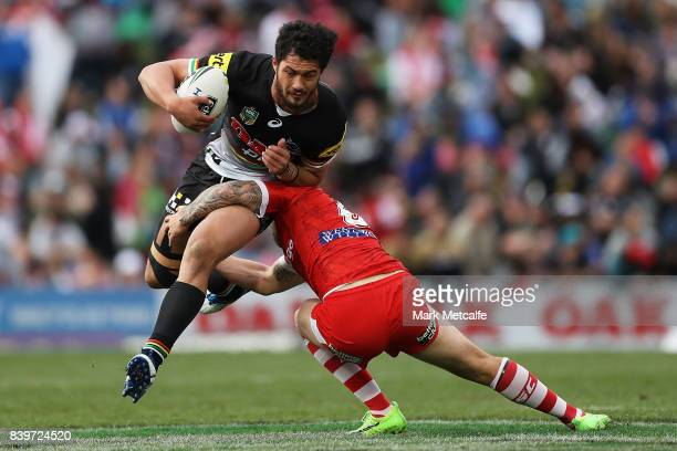 Corey Harawira Naera of the Panthers is tackled by Gareth Widdop of the Dragons during the round 25 NRL match between the Penrith Panthers and the St...