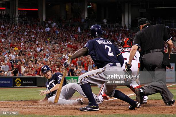 Corey Hart of the Milwaukee Brewers slides safely at home plate in the eighth inning to score a run to tie the game against the Cincinnati Reds at...