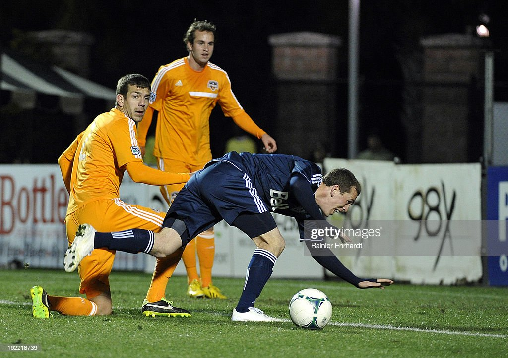Corey Hertzog #26 of the Vancouver Whitecaps FC falls as Eric Brunner #2 of the Houston Dynamo and teammate Brian Ownby #22 defend during the second half of a game at Blackbaud Stadium on February 20, 2013 in Charleston, North Carolina.