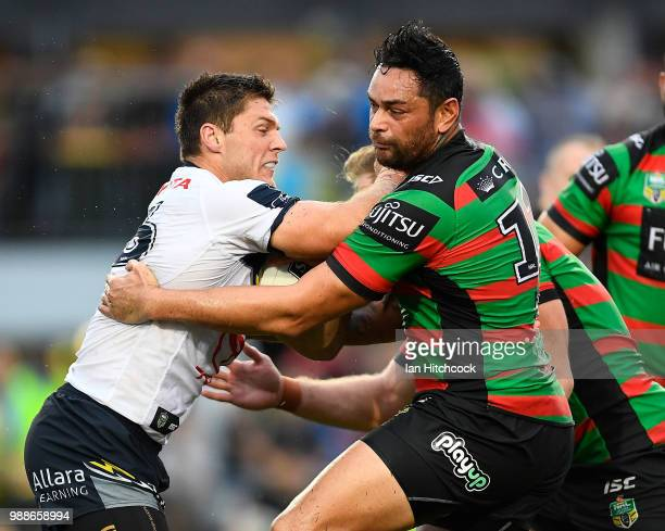 Corey Jensen of the Cowboys is tackled by John Sutton of the Rabbitohs during the round 16 NRL match between the South Sydney Rabbitohs and the North...