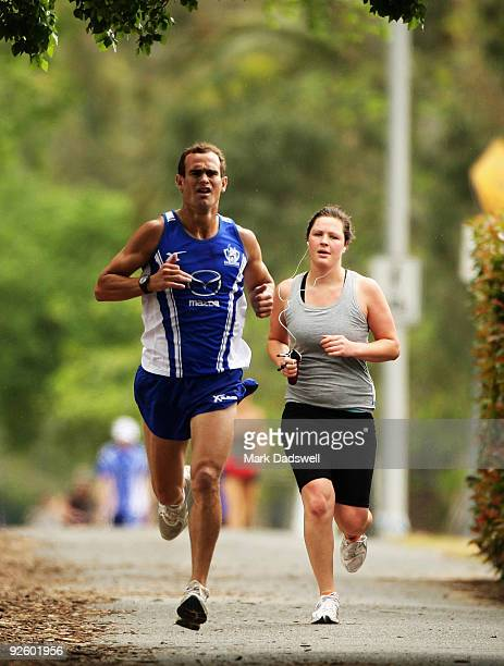 Corey Jones of the Kangaroos overtakes a recreational jogger in a lap of the dirt track during a North Melbourne Kangaroos AFL preseason training...
