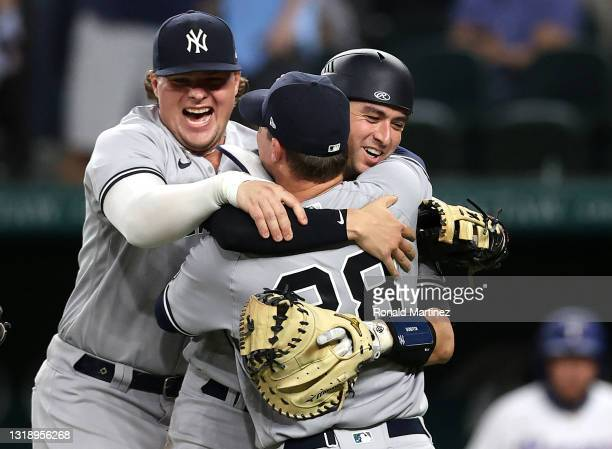 Corey Kluber of the New York Yankees celebrates a no-hitter with Luke Voit and Kyle Higashioka against the Texas Rangers at Globe Life Field on May...