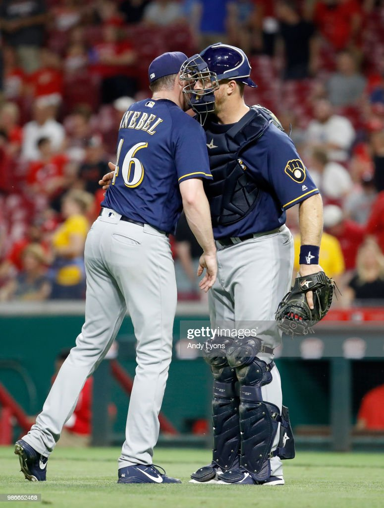 Corey Knebel #46 and Erik Kratz #15 of the Milwaukee Brewers share a hug after the last out of the 6-4 win against the Cincinnati Reds at Great American Ball Park on June 28, 2018 in Cincinnati, Ohio.