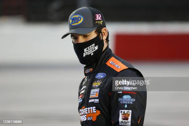 Corey LaJoie driver of the Keen Parts Thank a Hero Ford stands on the grid prior to the NASCAR Cup Series Toyota 500 at Darlington Raceway on May 20...