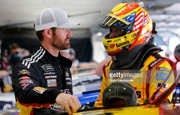 Corey LaJoie driver of the Samaritan's Feet Ford talks with Michael McDowell driver of the Love's Travel Stops Ford during practice for the Monster...
