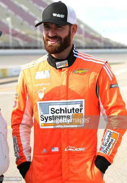 Corey LaJoie driver of the Schluter Systems Chevrolet walks to his car during qualifying for the Monster Energy NASCAR Cup Series Consmers Energy 400...