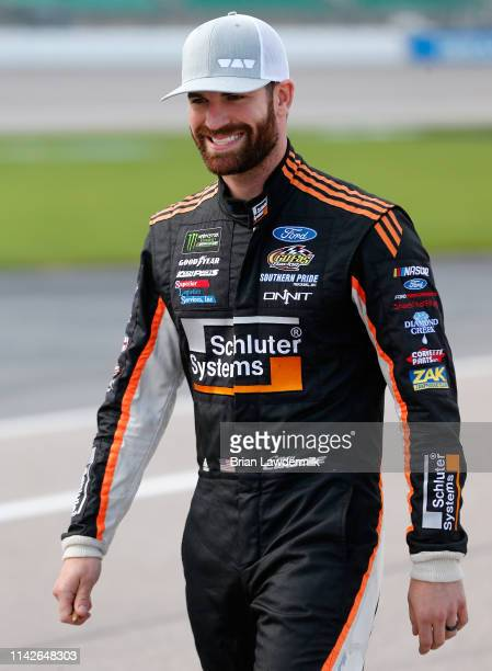 Corey LaJoie driver of the Schluter Systems Ford walks down pit road during qualifying for the Monster Energy NASCAR Cup Series Digital Ally 400 at...