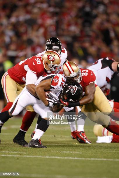 Corey Lemonier and Demarcus Dobbs of the San Francisco 49ers tackle Jacquizz Rodgers of the Atlanta Falcons during the game at Candlestick Park on...