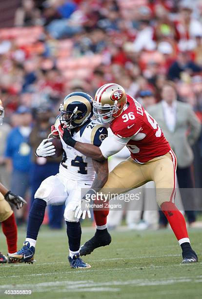 Corey Lemonier of the San Francisco 49ers tackles Isaiah Pead of the St Louis Rams during the game at Candlestick Park on December 1 2013 in San...