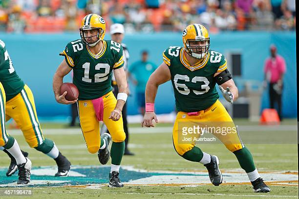 Corey Linsley leads the way for Aaron Rodgers the Green Bay Packers as he runs with the ball against the Miami Dolphins on October 12, 2014 at Sun...