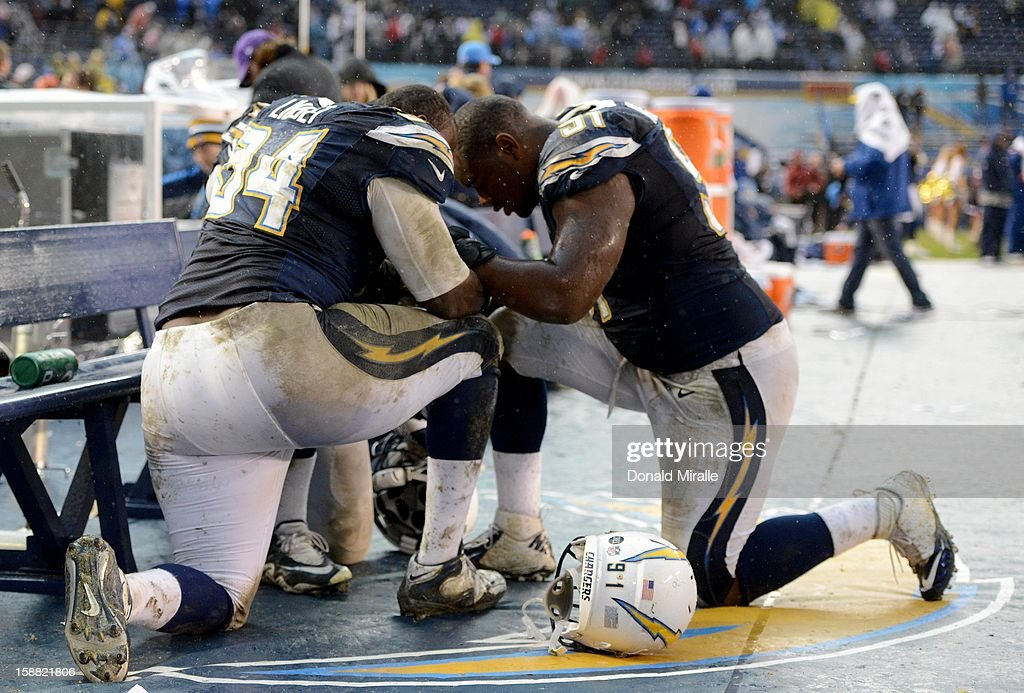 Corey Liuget #94 and Kendall Reyes #91of the San Diego Chargers pray on the sidelines after the 24-21 win over the Oakland Raiders on December 30, 2012 at Qualcomm Stadium in San Diego, California.