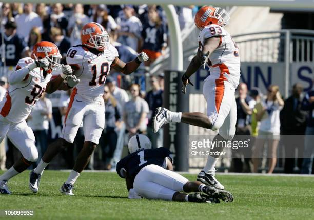 Corey Liuget of the Illinois Fighting Illini celebrates with teammates Michael Buchanan and Nate Bussey after sacking Rob Bolden of the Penn State...