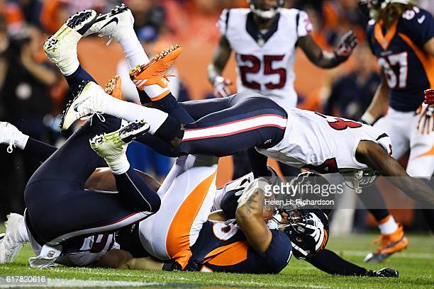 Corey Moore of the Houston Texans, Andre Hal and Brian Cushing tackle Devontae Booker of the Denver Broncos during the second quarter on Monday,...