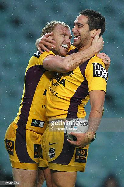 Corey Norman of the Broncos celebrates scoring a try with team mate Peter Wallace during the round 14 NRL match between the Sydney Roosters and the...