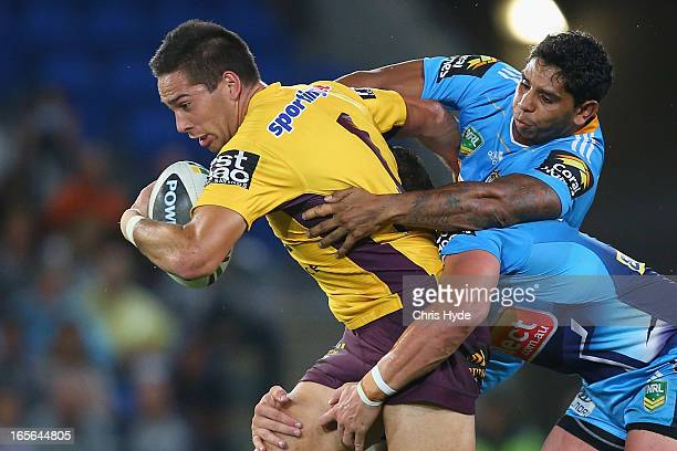 Corey Norman of the Broncos is tackled by Albert Kelly of the Titans during the round five NRL match between the Gold Coast Titans and the Brisbane...