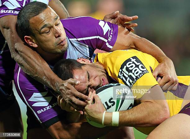 Corey Norman of the Broncos is tackled by Will Chambers of the Storm during the round 17 NRL match between the Melbourne Storm and the Brisbane...