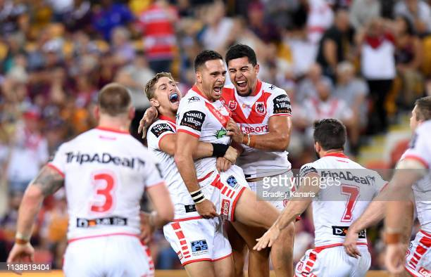 Corey Norman of the Dragons is congratulated by team mates after kicking the winning field goal during the round 3 NRL match between the Brisbane...