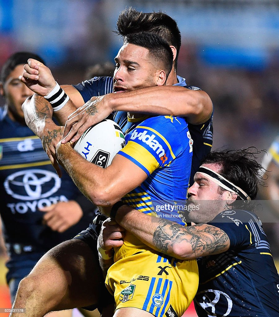 Corey Norman of the Eels is tackled by Ethan Lowe and James Tamou of the Cowboys during the round eight NRL match between the North Queensland Cowboys and the Parramatta Eels at 1300SMILES Stadium on April 23, 2016 in Townsville, Australia.