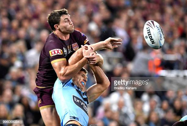 Corey Oates of Queensland and Tom Trbojevic of the Blues challenge for the ball during game three of the State of Origin series between the...