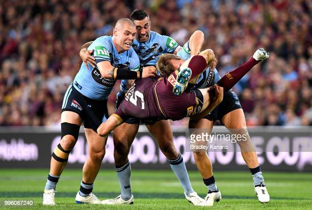 Corey Oates of Queensland is picked up in the tackle by Jake Trbojevic of the Blues during game three of the State of Origin series between the...