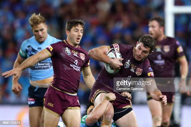 Corey Oates of Queensland is tackled during game three of the State of Origin series between the Queensland Maroons and the New South Wales Blues at...