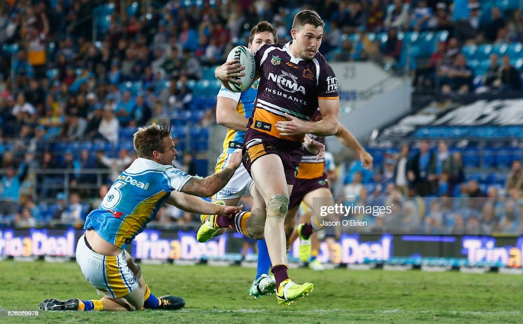 Corey Oates of the Broncos breaks the tackle of Kane Elgey to score a try during the round 22 NRL match between the Gold Coast Titans and the Brisbane Broncos at Cbus Super Stadium on August 5, 2017 in Gold Coast, Australia.