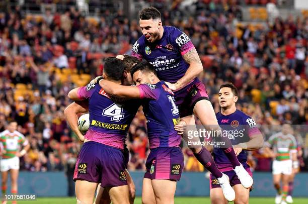Corey Oates of the Broncos is congratulated by team mates after scoring a try during the round 23 NRL match between the Brisbane Broncos and the...