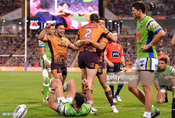Corey Oates of the Broncos is congratulated by team mates after scoring a try during the round 16 NRL match between the Brisbane Broncos and the...