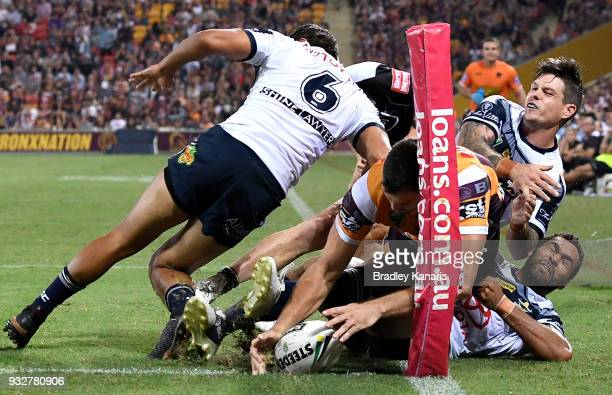 Corey Oates of the Broncos is stopped from scoring a try by the Cowboys defence during the round two NRL match between the Brisbane Broncos and the...