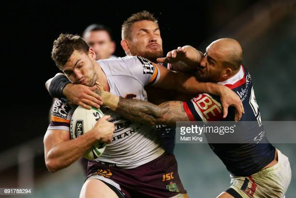 Corey Oates of the Broncos is tackled by Jared WaereaHargreaves and Blake Ferguson of the Roosters during the round 13 NRL match between the Sydney...