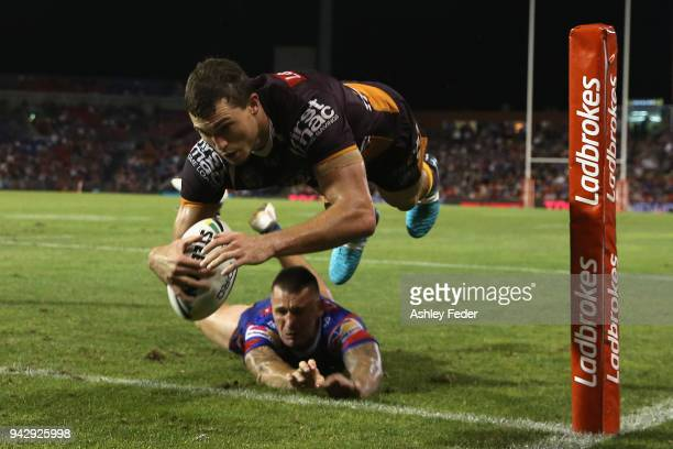 Corey Oates of the Broncos scores a try tackled by Shaun KennyDowall of the Knights during the round five NRL match between the Newcastle Knights and...