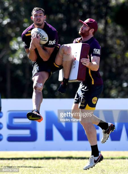 Corey Oates takes a catch as he is pressured by former Brisbane Lions player Daniel Merrett during a Brisbane Broncos NRL training session on...
