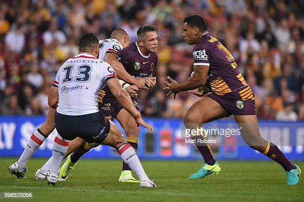 Corey Parker of the Broncos passes the ball under pressure to Tevita Pangai Junior during the round 26 NRL match between the Brisbane Broncos and the...
